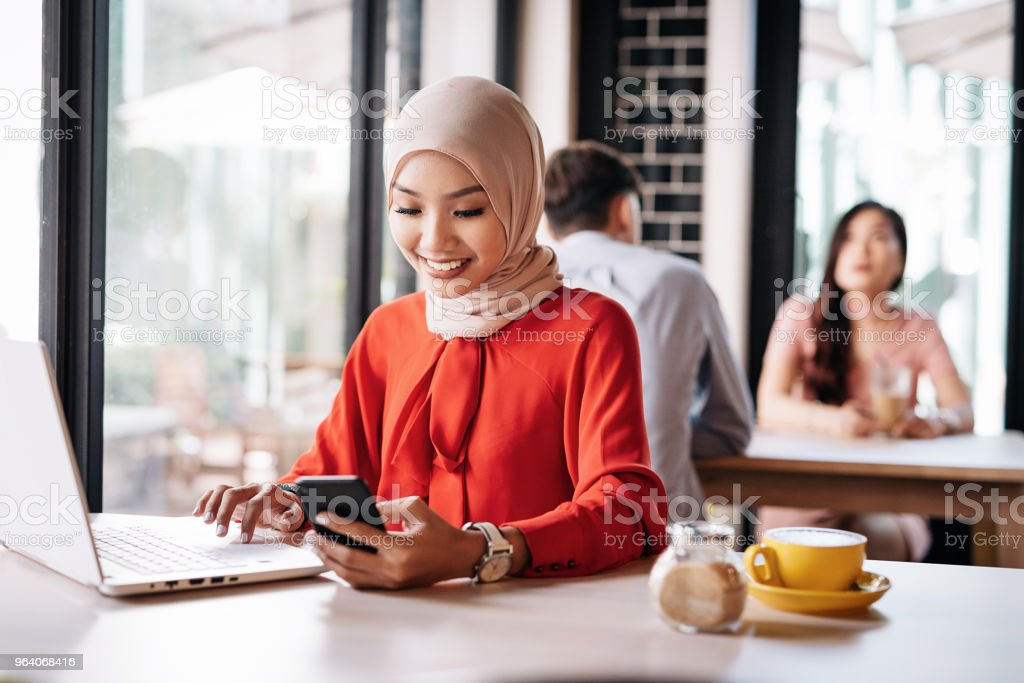 Businesswoman synchronizes mobile apps and laptop software - Royalty-free 20-29 Years Stock Photo