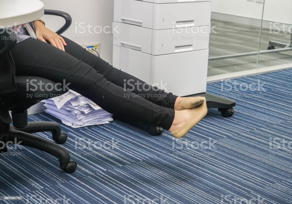 businesswoman take off her shoes to relax on her chair in office zbiór zdjęć royalty-free