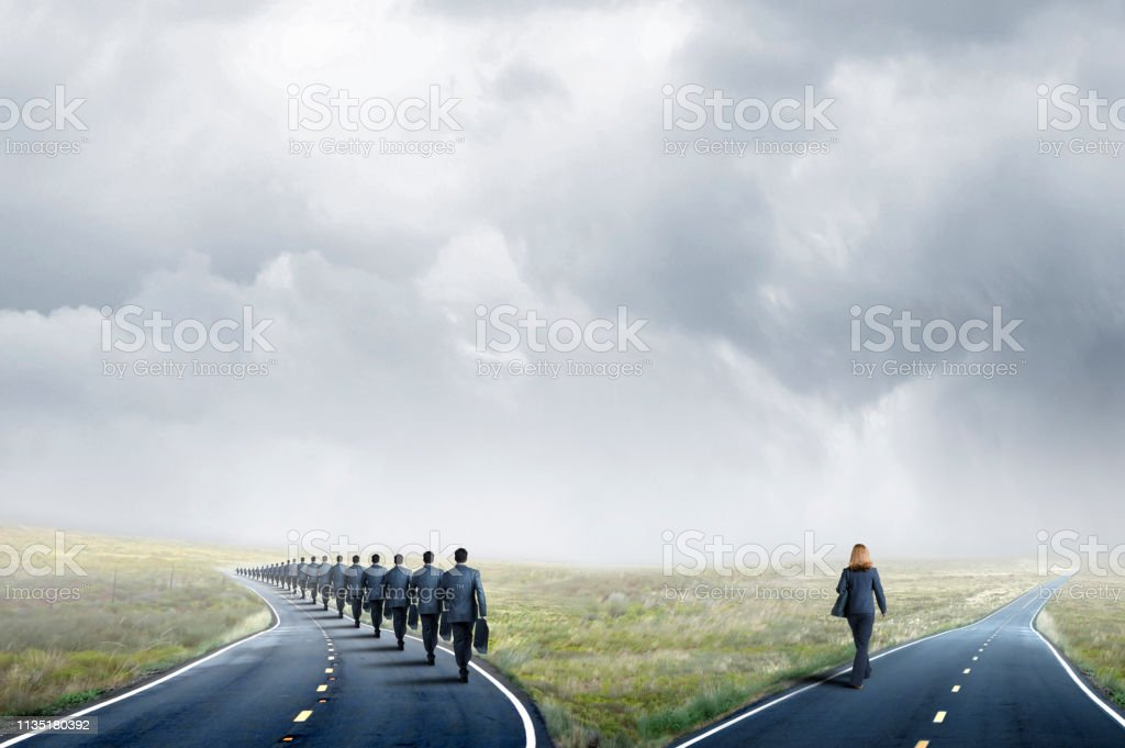 Businesswoman Takes A Different Road Than A Long Line Of Businessmen stock photo