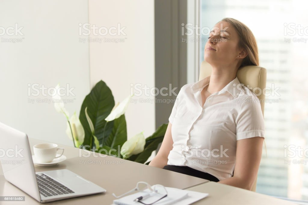 Businesswoman takes short time-out in office work stock photo