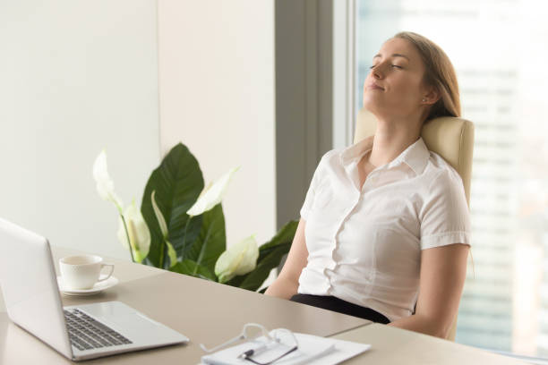 businesswoman takes short time-out in office work - profondo foto e immagini stock