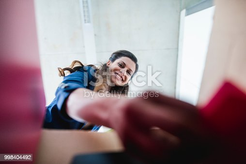 istock Businesswoman taking a file out of a box in the office 998404492