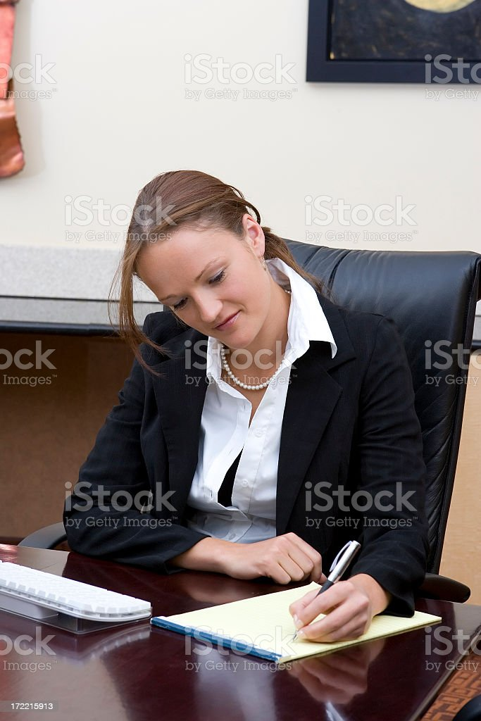 Businesswoman Taking Notes at Desk royalty-free stock photo