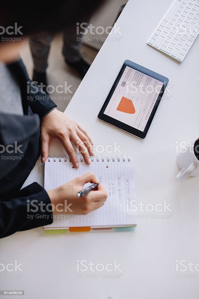 Businesswoman taking notes in notepad stock photo