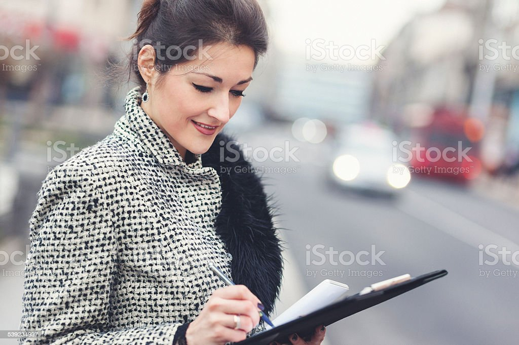 Businesswoman taking notes outdoors royalty-free stock photo