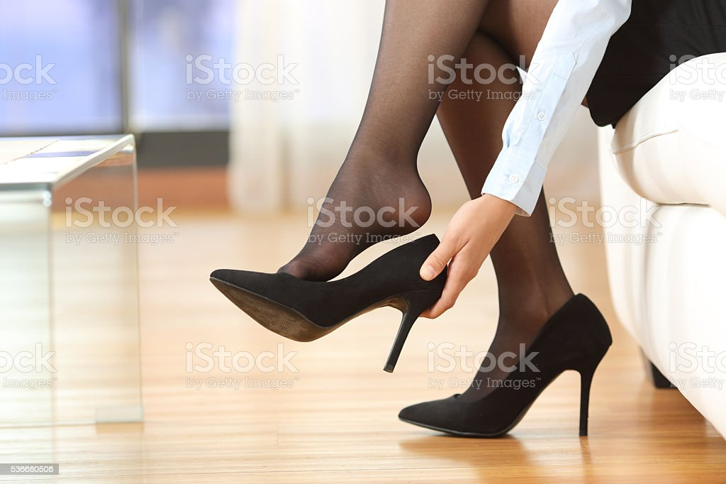 Businesswoman taking off shoes stock photo