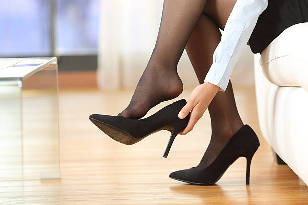 businesswoman taking off shoes - human foot stock photos and pictures