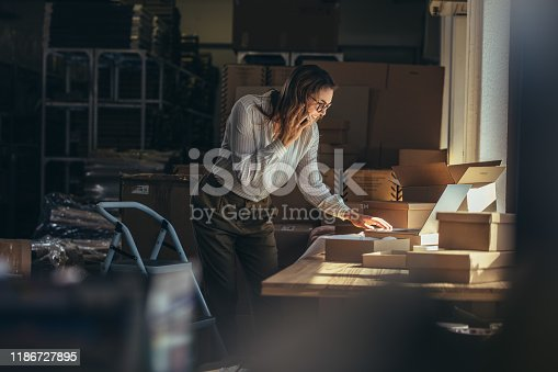 Online store businesswoman working on laptop and taking on the phone. Female business professional taking order on phone.