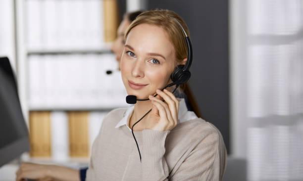 Geschäftsfrau spricht per Headset, während sie im Büro sitzt. Callcenter und diverse Menschengruppe in der Wirtschaft – Foto