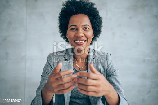 African-american elegant female entrepreneur discussing while having a conference call in the office.    Portrait of confident ethnicity female employee looking at camera  talking on video call in the office.