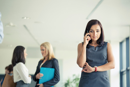 Businesswoman Talking On Cell Phone In An Office Stock Photo - Download Image Now