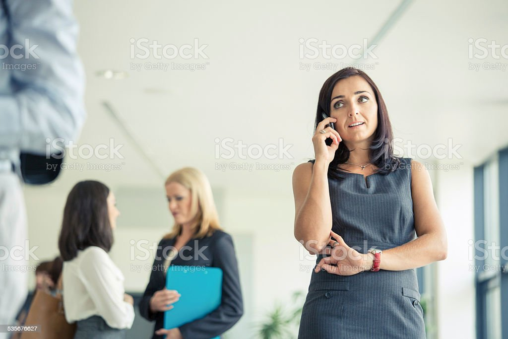 Businesswoman talking on cell phone in an office An attractive businesswoman talking on mobile phone in an office with her co-workers standing in the background.  2015 Stock Photo