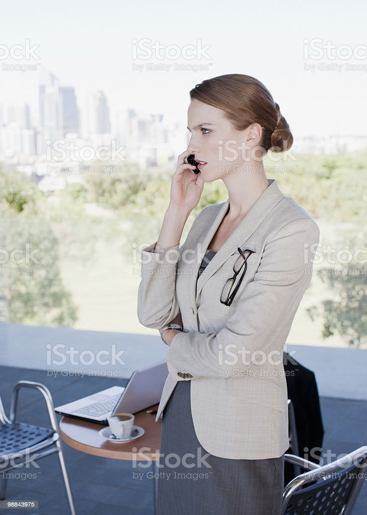 Businesswoman talking on cell phone in cafe royalty free stockfoto