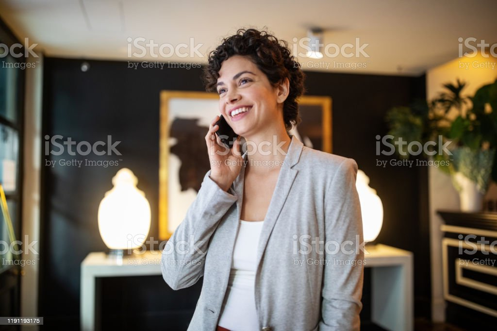 Businesswoman talking on cell phone in hotel lobby - Royalty-free Adult Stock Photo