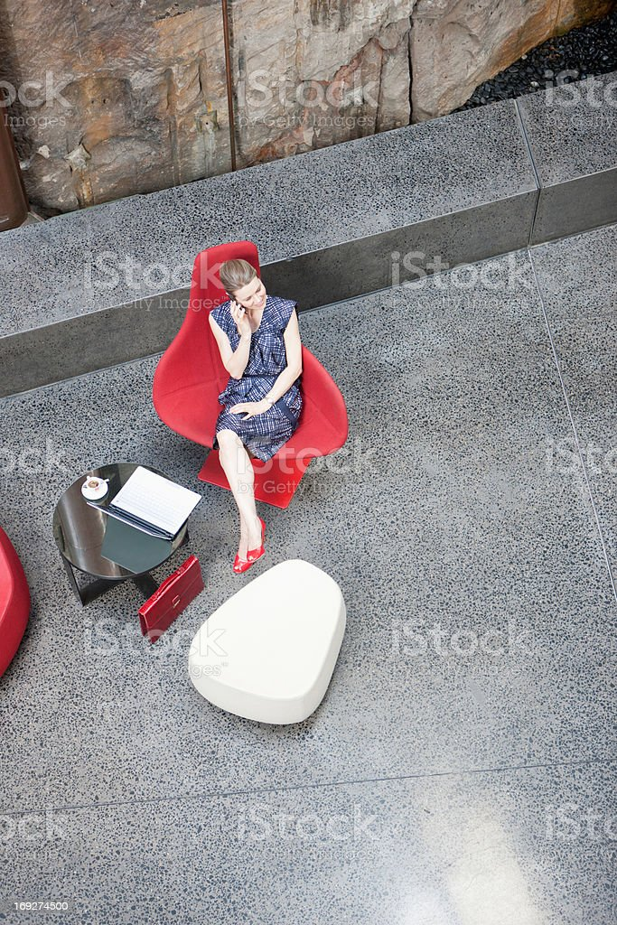 Businesswoman talking on cell phone in modern lobby stock photo