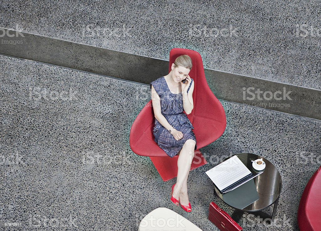 Businesswoman talking on cell phone in modern lobby royalty-free stock photo