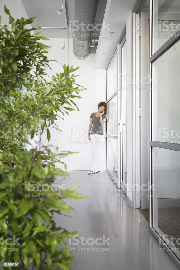 Bizneswoman rozmawia przez telefon komórkowy w biurze Korytarz zbiór zdjęć royalty-free