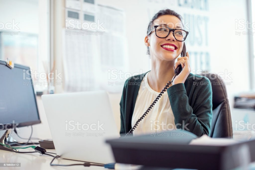 Businesswoman talking on landline phone in office stock photo