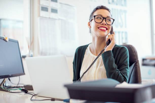Businesswoman talking on landline phone in office stock photo