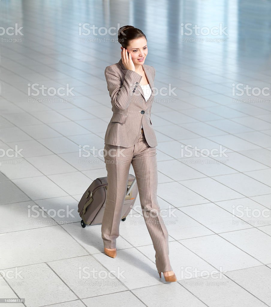 Businesswoman talking on mobile phone in airport royalty-free stock photo