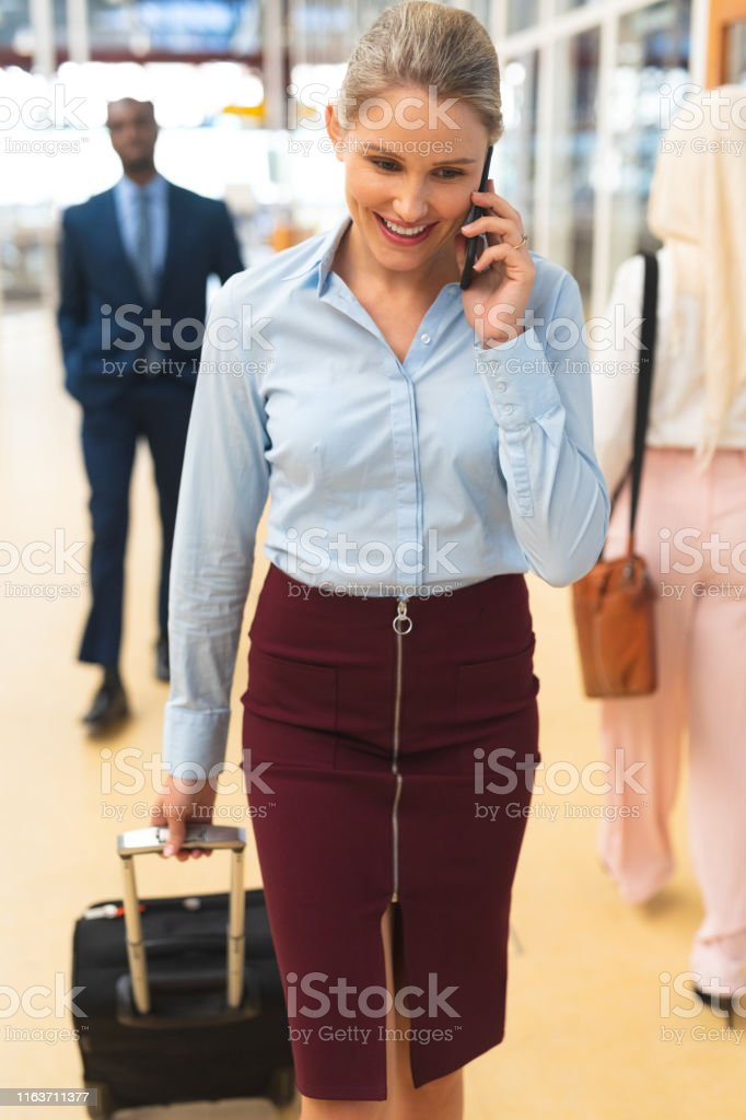 Front view of Caucasian businesswoman talking on mobile phone while...
