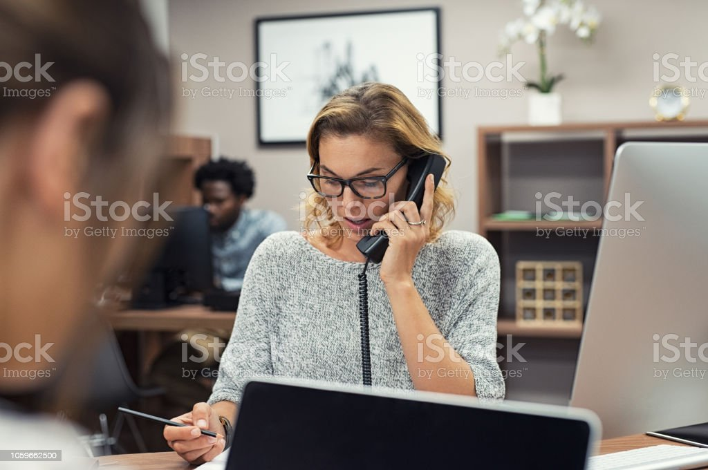 Businesswoman talking on phone at office Mature businesswoman talking on phone in office. Casual business woman talking on landline phone in a creative agency. Beautiful blonde receptionist with eyeglasses taking client details over phone. 30-39 Years Stock Photo