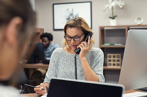 Businesswoman Talking On Phone At Office Stock Photo - Download Image Now