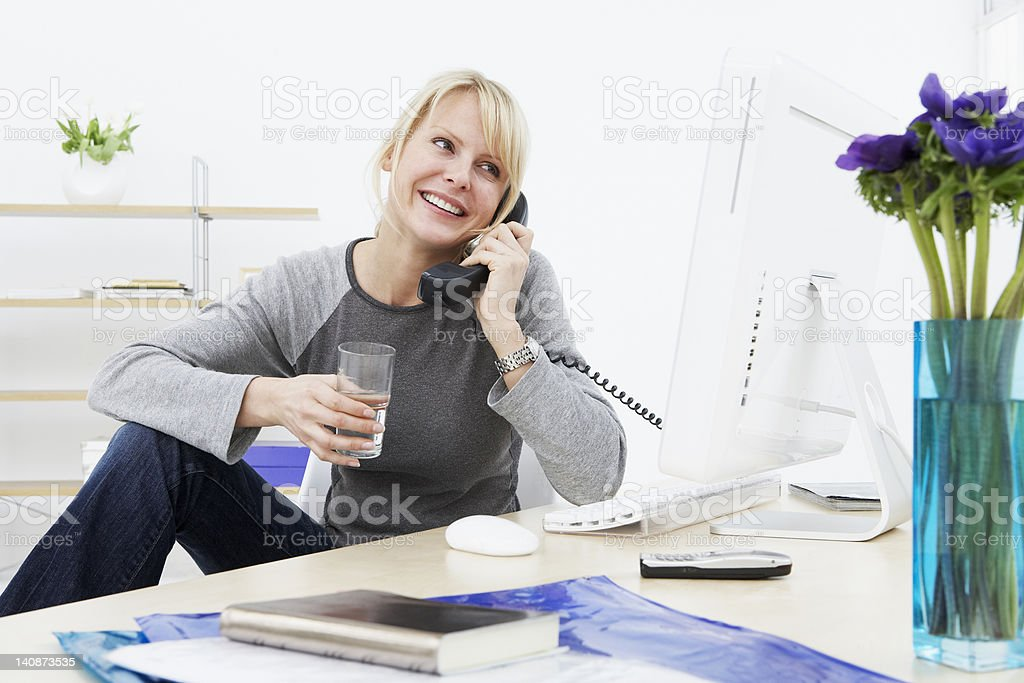 Businesswoman talking on phone at work stock photo