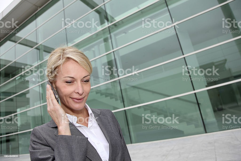 Businesswoman talking on phone near a green building glass royalty-free stock photo