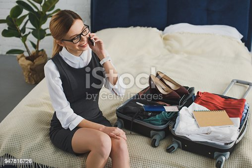 istock businesswoman talking on smartphone while packing suitcase for business trip 947816726