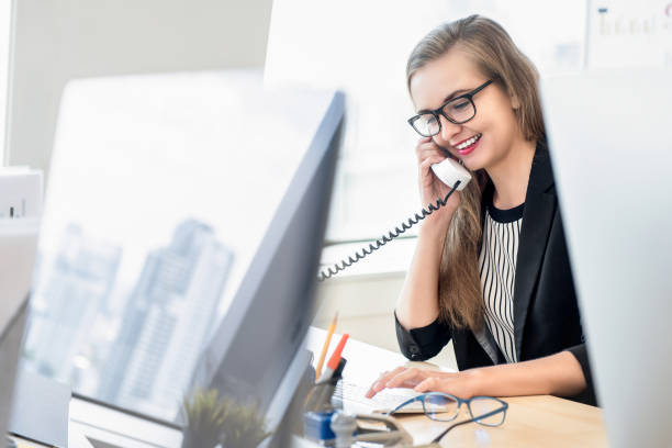 businesswoman talking on the phone with customer at work - assistant stock pictures, royalty-free photos & images