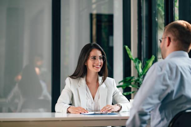 Mujer de negocios hablando con un cliente en la reunión de negocios. - foto de stock