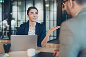 istock Businesswoman talking to a colleague 1282663910