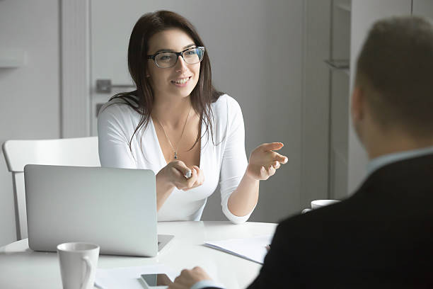 Businesswoman talking to a man at the desk stock photo