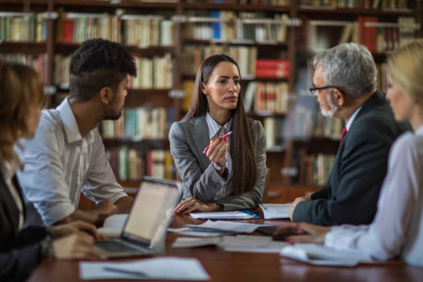 businesswoman talking to her team about new business ideas on a meeting. - lawyers stock photos and pictures