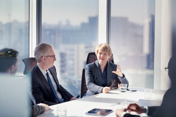 Businesswoman talking with colleagues in meeting stock photo