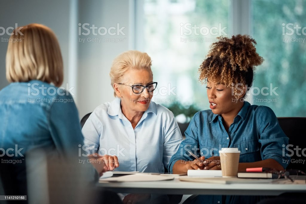 Businesswoman talking with executives at desk Businesswoman talking with executives at desk. Business professionals are working on start-up. They are sitting in office. 35-39 Years Stock Photo