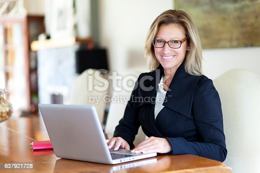 istock Businesswoman teleworking at home. On a Laptop. Smiling 637921728