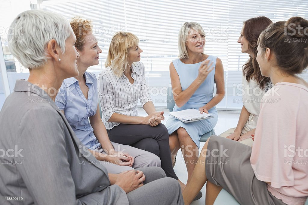 Businesswoman telling a story to her colleagues stock photo