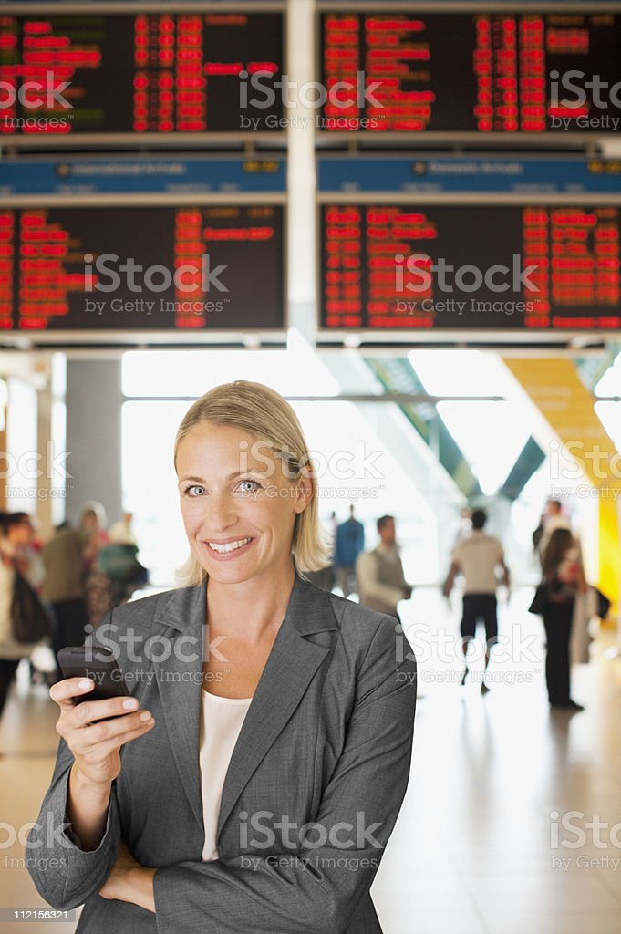 Businesswoman text messaging on cell phone in airport royalty-free stock photo