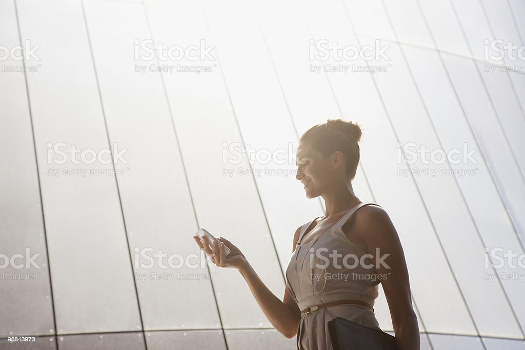 Businesswoman text messaging on cell phone outdoors 免版稅 stock photo