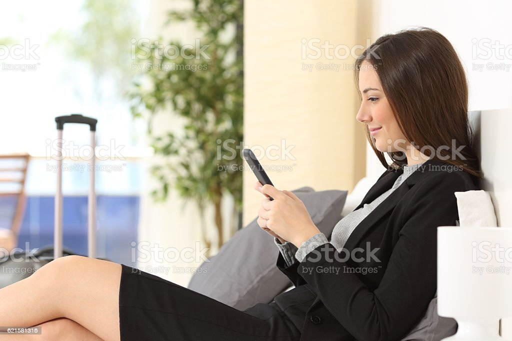Businesswoman texting on phone in an hotel stock photo