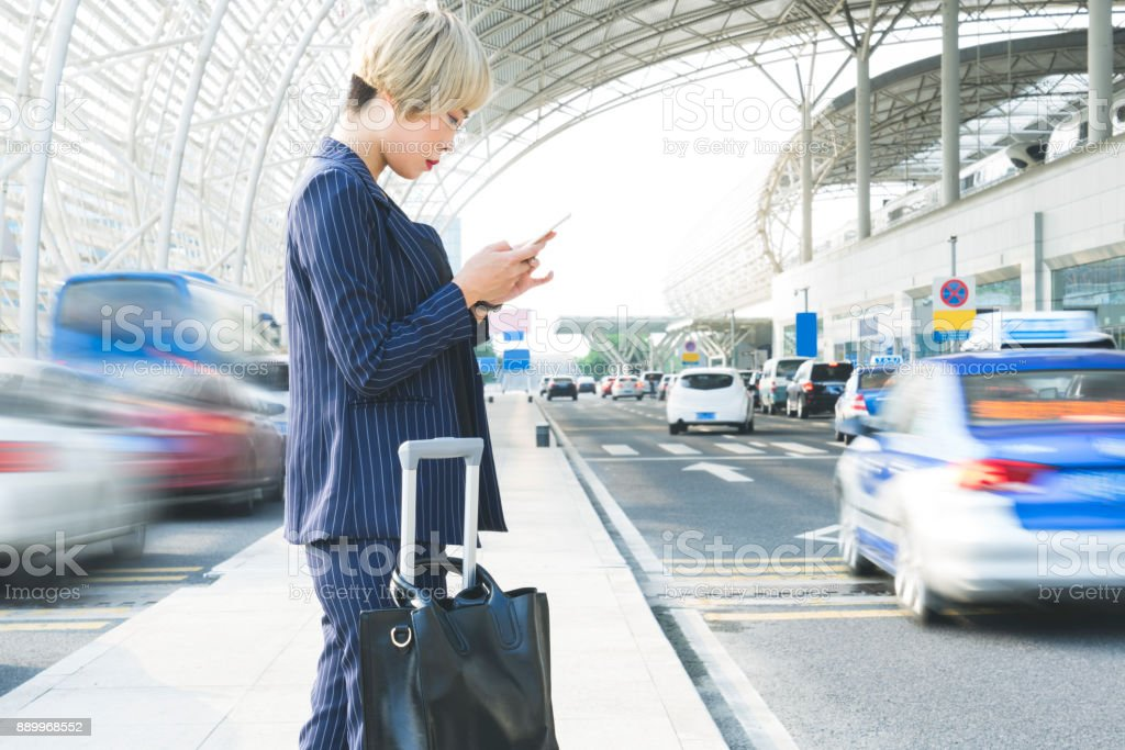 businesswoman texting on phone with suitcase outside airport/station stock photo