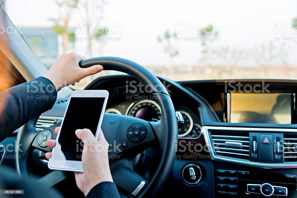 businesswoman texting while driving stock photo