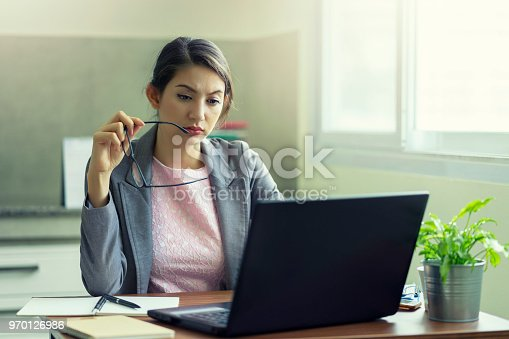 692461598 istock photo Businesswoman thinking and frustrated on his work and out of control. Stress and headache, She holding glasses and tried to new project. 970126986