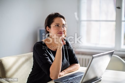 Businesswoman sitting in front of a laptop and thinking. Female is sitting at boardroom table with her laptop.