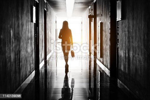 Businesswoman through the office corridor.