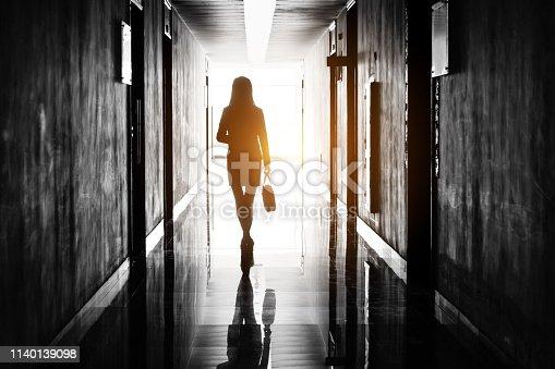 Businesswoman through the office corridor.