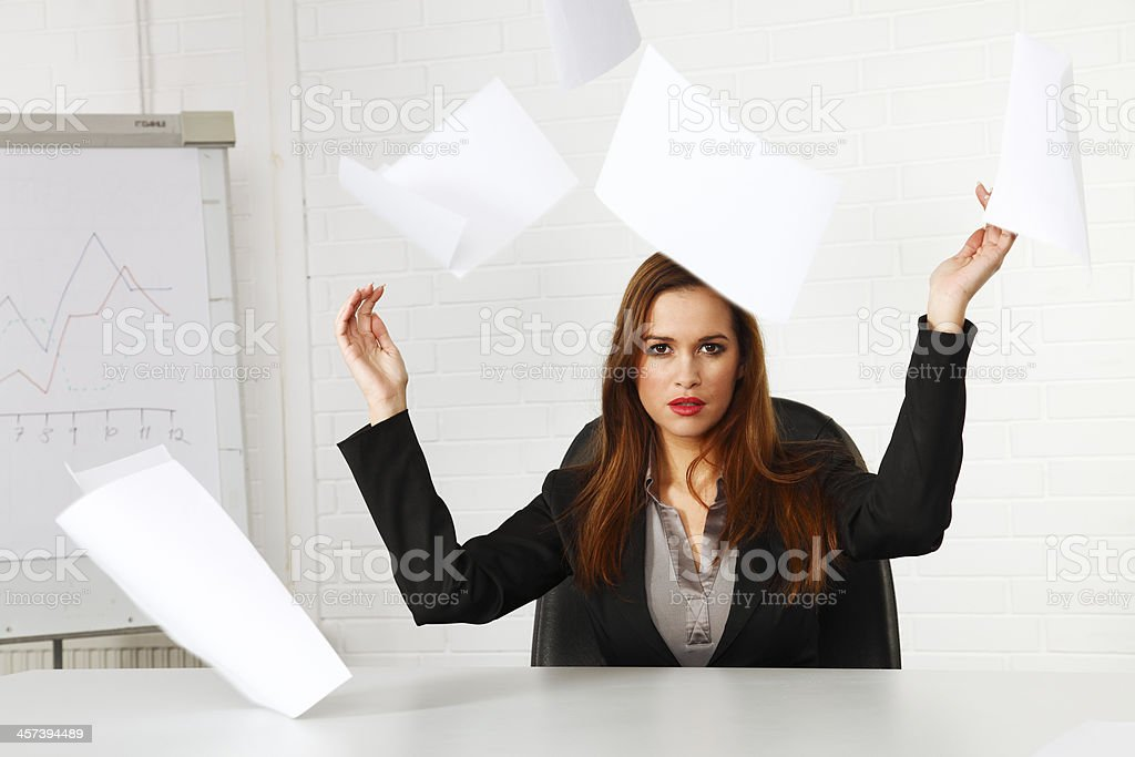 Businesswoman throwing paperwork in the air royalty-free stock photo