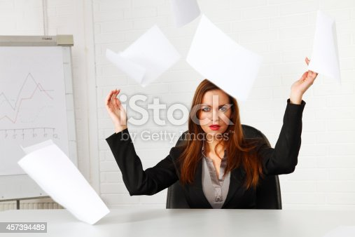 187928332 istock photo Businesswoman throwing paperwork in the air 457394489